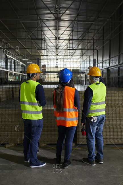 Rear view of workers standing at grid in factory