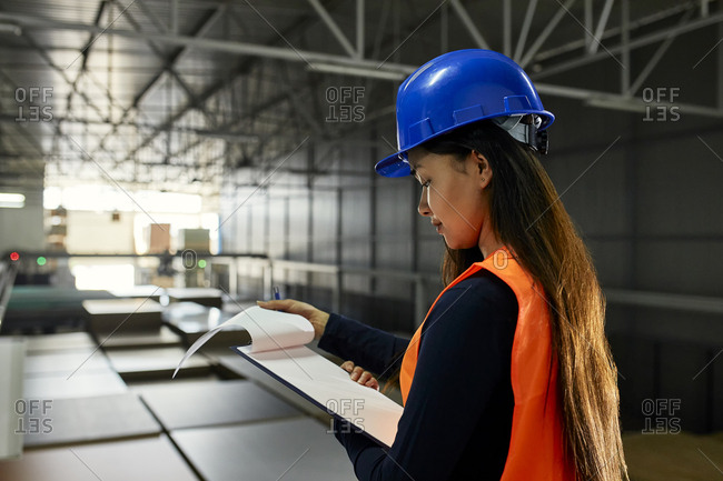 Female worker checking documents in factory warehouse