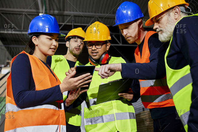 Workers in factory warehouse talking and using tablet