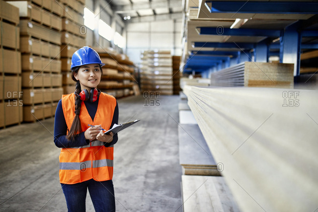 Smiling female worker with clipboard in factory warehouse