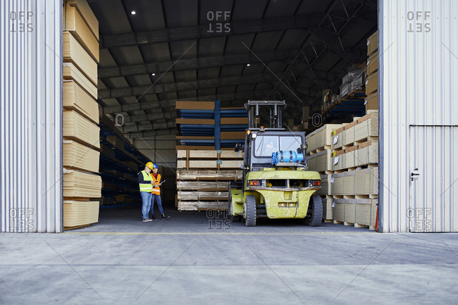 Two workers standing in factory warehouse next to forklift