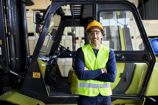 Portrait of confident worker at forklift in factory