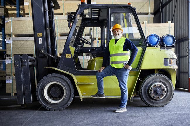 Portrait of confident mature worker at forklift in factory