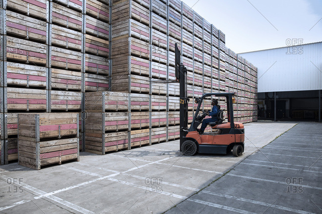 Worker on forklift and stacks of crates on factory yard
