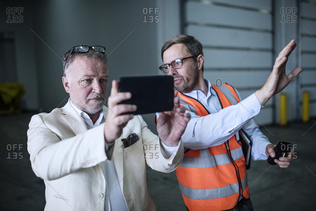 Man in reflective vest talking to businessman with cell phone in industrial hall
