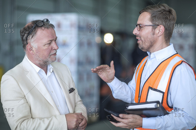 Businessman and man in reflective vest talking in industrial hall