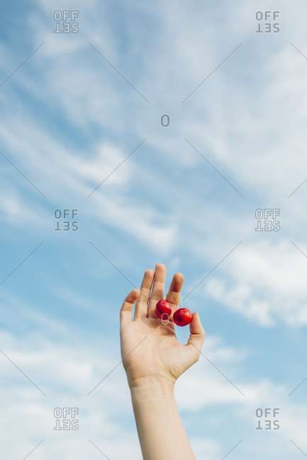 Cherries in hand against the blue sky