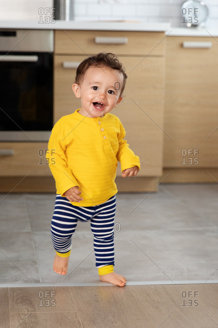 Baby making first steps in kitchen