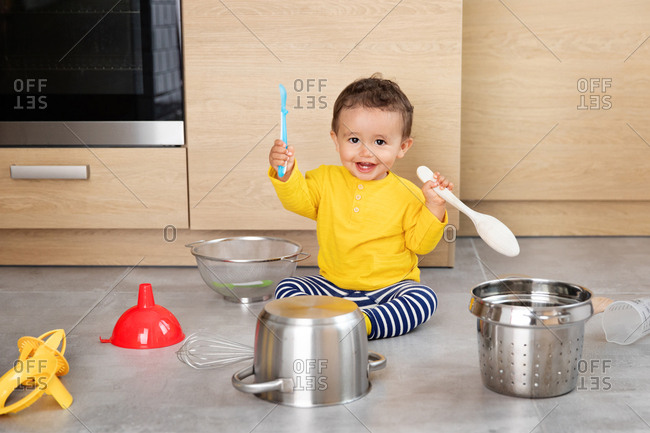 Happy baby playing with kitchenware on kitchen floor