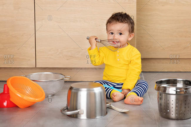 Cute baby playing with utensils in kitchen