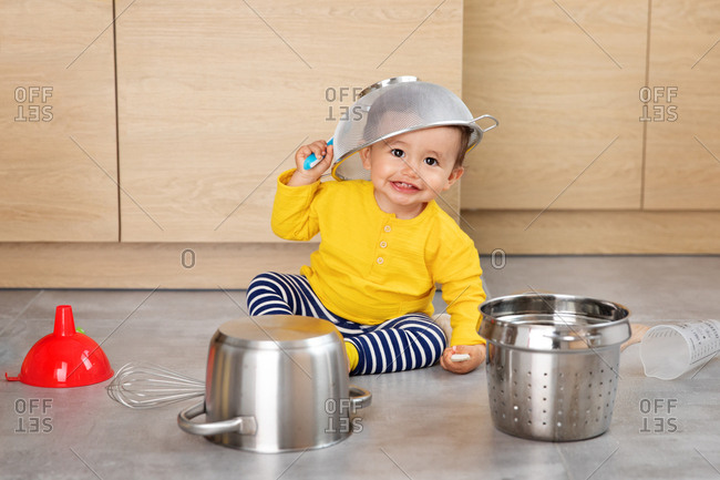 Happy baby playing with kitchen utensils with colander on top of head