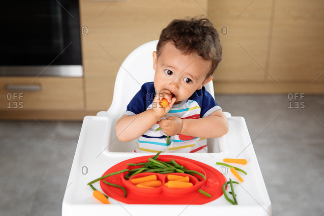 Baby boy in high chair eating vegetables