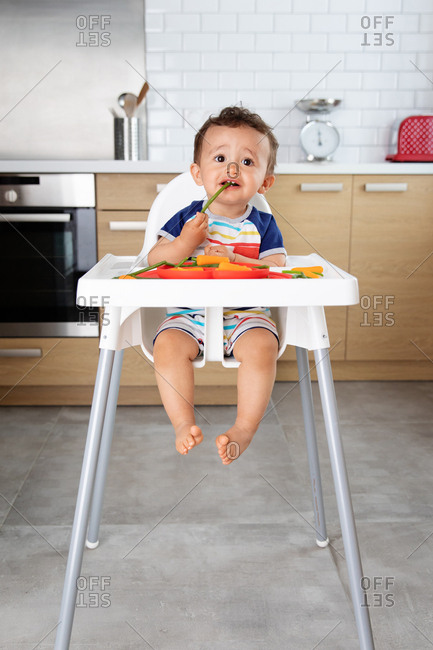 Baby boy in high chair eating green beans
