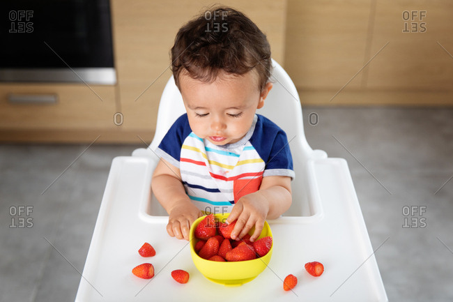 Baby boy in high chair picking strawberries from bowl