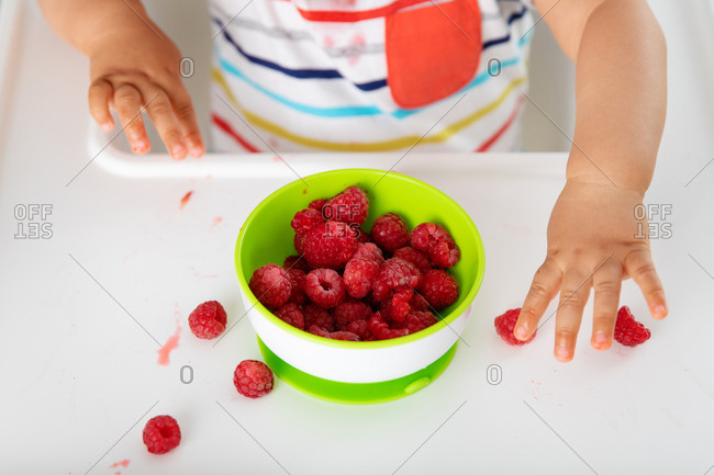Close up of baby's hands touching strawberries in high chair