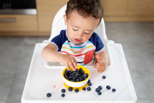 Baby boy in high chair picking blueberries from bowl