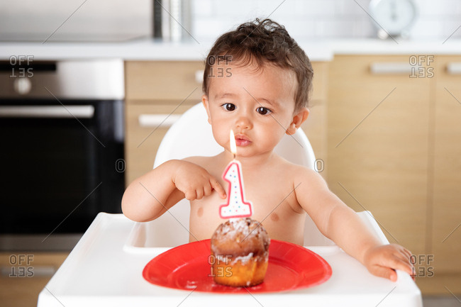 Baby blowing candle on first birthday