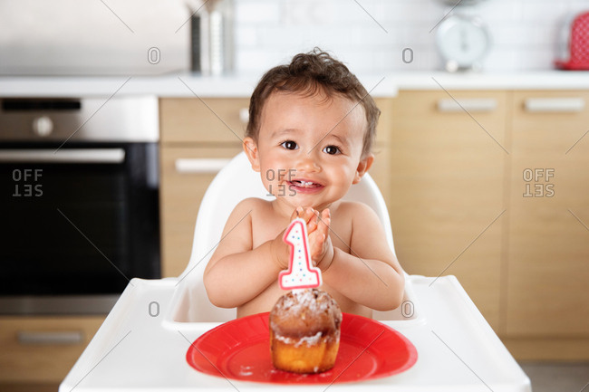 Happy baby in high chair with cake celebrating first birthday