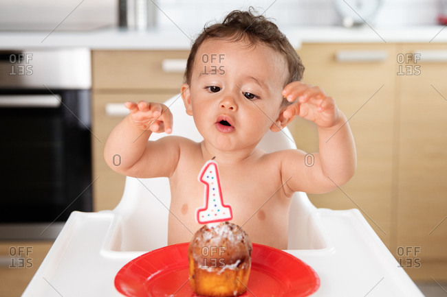 Funny baby in high chair reaching out to candle on first birthday