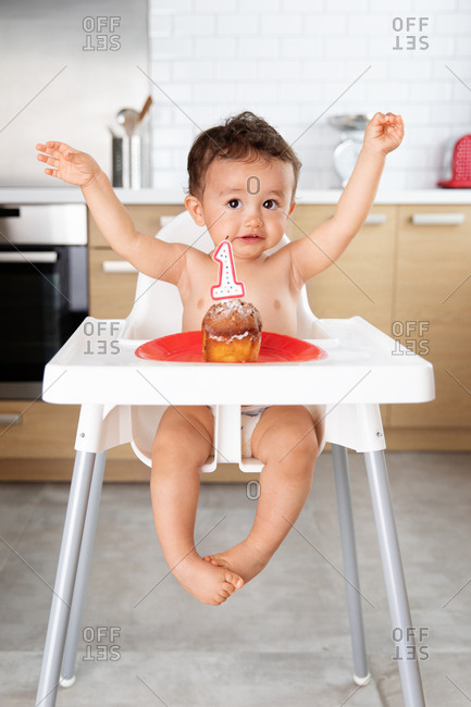 Happy baby in high chair with arms in the air celebrating first birthday