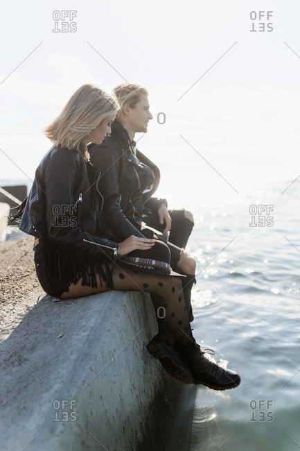 Side view of young blonde couple sitting in a rock in the sea