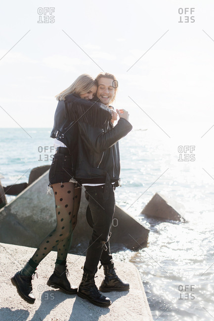 Rear view of young rocker couple embraced in front of the sea in a sunny day