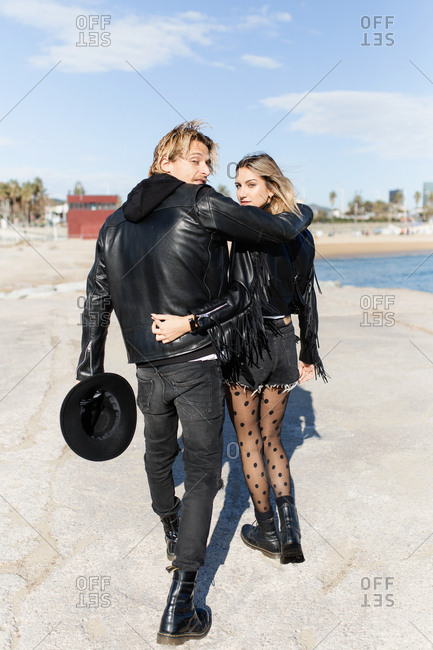 Rear view of young rocker couple turned looking at camera