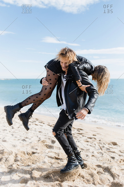 Rocker blonde couple run together by the beach in a sunny day