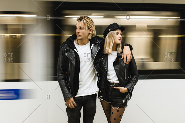 Front view of young rocker couple on the subway train in motion background