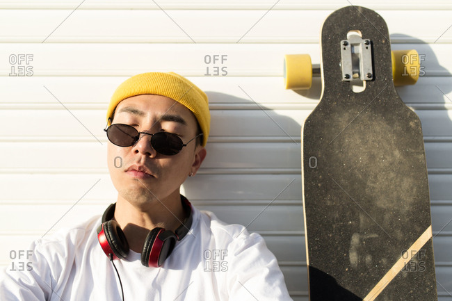 Portrait of young asian boy with yellow hat sunglasses and headphones is sitting in front of white gate relaxing in a sunset