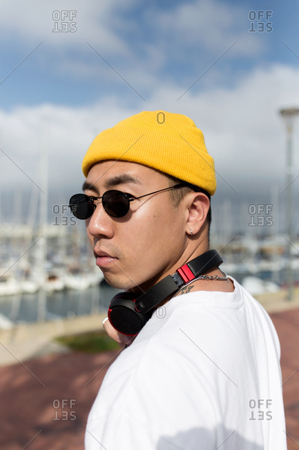 Portrait of young asian boy with yellow beanie sunglasses and headphones turned on looking at camera