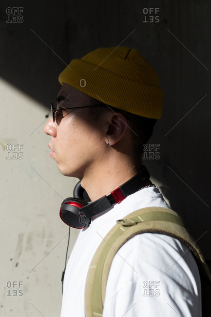 Side view of young asian man with yellow beanie sunglasses and headphones cover middle face by shadows wall background