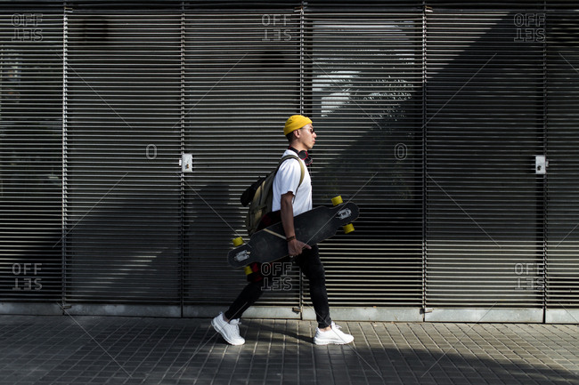 Side view of young asian man with yellow beanie sunglasses and headphones walking by the street wall background
