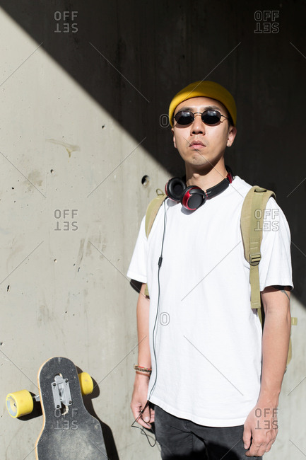 Young asian man with bag sunglasses and headphones in front of wall looking at sun shadows background