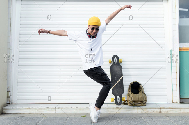 Front view of young asian man with yellow hat and headphones dancing in front of white gate bag and skate background