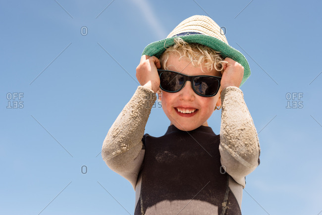 Blonde boy putting on sunglasses to protect his eyes from the sun