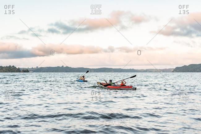 Siblings kayaking on a lake at sunset