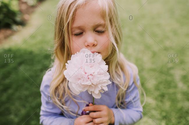Blonde little girl smelling a flower