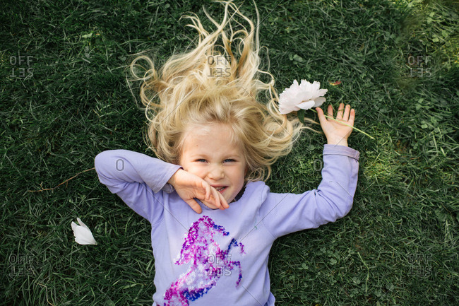 Overhead view of blonde girl lying in grass holding a flower