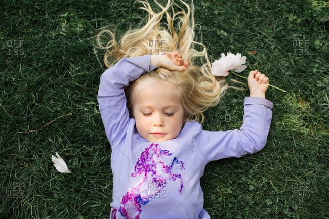 Blonde girl lying in grass holding a flower
