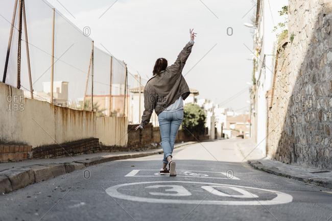 Young beautiful woman walking dancing on city street on daylight