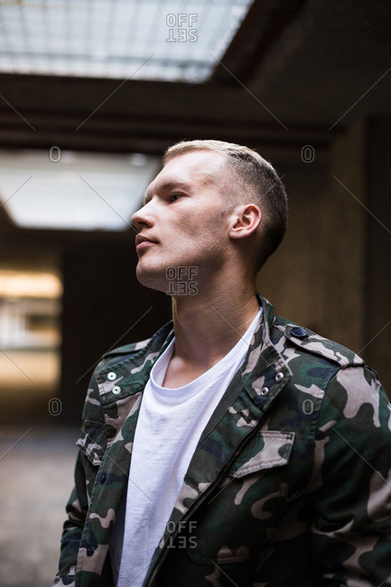 Positive young guy in trendy outfit looking away