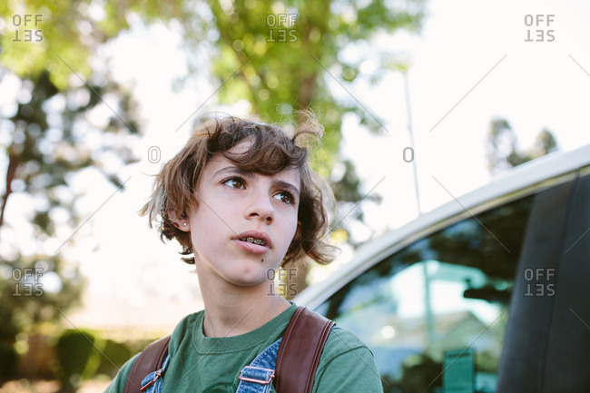 Portrait of teen girl looking into the distance while next to car