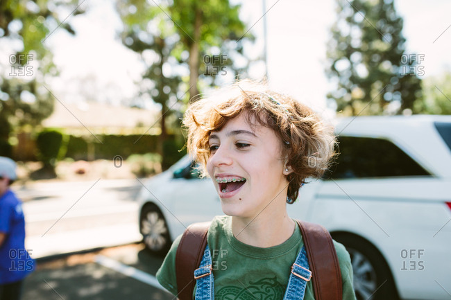 Teen girl laughs while standing outside in a parking lot