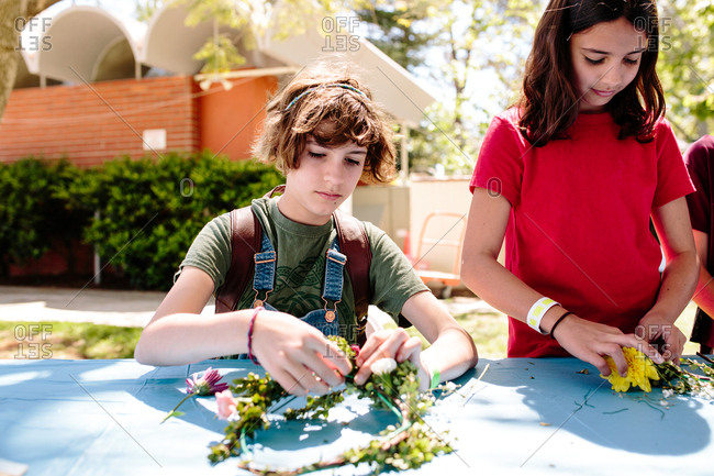 Teen girls working on making flower crowns outside at a table