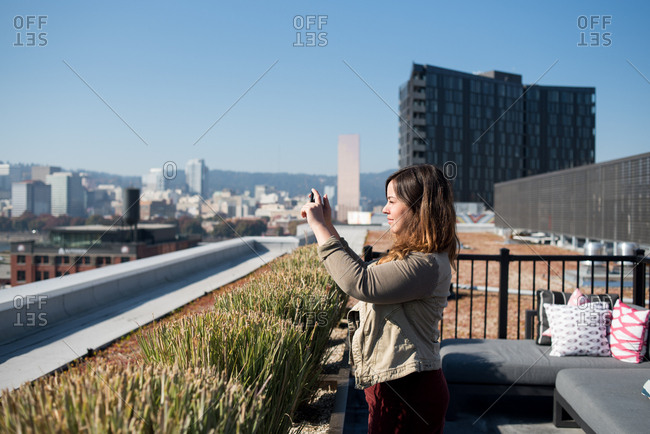 Woman on Portland rooftop taking photo of city with smart phone