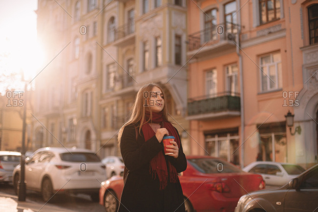 Thoughtful woman with coffee cup walking on street on sunny day