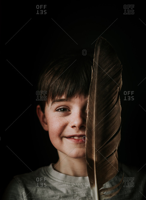 Portrait of young boy holding a large feather over half of his face.