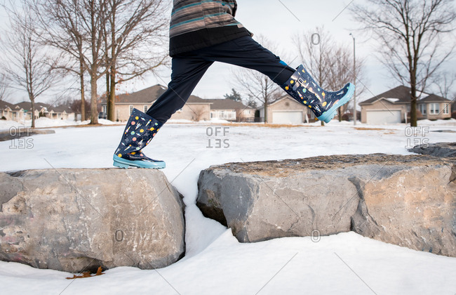 Cropped image of a boy's legs taking big step across large rocks.
