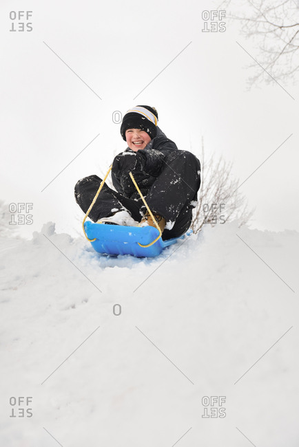 Smiling boy sitting on a toboggan on snowy hill on a winter day.